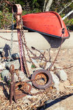 Old red rowboat lays on the coast near anchors Stock Photography