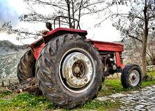 Old red rusty tractor parked by the road. Dimitsana village, Gre. Ece Stock Images