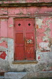 Old red shutters and peeling paint Stock Photo