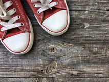 Old red sneakers on the gray wooden background Stock Photography