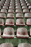 Old Red Stadium Chairs. Empty old red plastic chairs in a stadium stock image