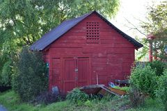 Old Red storage tin roofed barn. In shade royalty free stock image