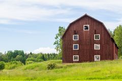 An Old Red Swedish Barn. Scenic View of an Old Swedish Barn with a Blue Cloudy Sky Royalty Free Stock Photography