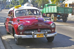 Old red taxi driving through the streets of Havana Cuba Royalty Free Stock Photos