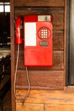 Old red telephone on a wooden wall. stock photos