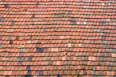 Old red tile roof pattern. Rows of weathered red tiles with moss stock photos