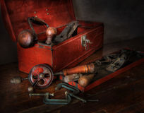 Old Red Toolbox Wood Working Tools. An old grungy red metal tool box with hand drill, brace and bit, clamps and wood smoothing plane Stock Image