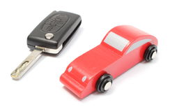 Old red toy car and vehicle key on white background Royalty Free Stock Photos