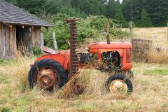 Old Red Tractor. An old red farm tractor in a small country farm that had not been used for a while. While it normally cuts grass, in this case, it was royalty free stock images