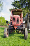 Old red tractor on grass in farm Royalty Free Stock Image
