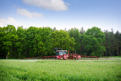 Old red tractor spraying fertilizer or herbicide on a field near Royalty Free Stock Image