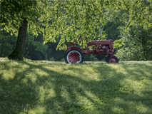 Old Red Tractor in the Sun. An old unused red tractor on a hillside in the morning sunlight stock photography