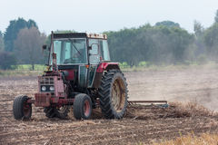 Old red tractor working field Royalty Free Stock Photo