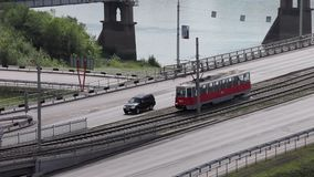 Old red tram with people walk on bridge stock video footage