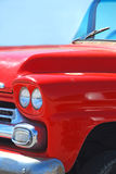 Old Red Truck. Antique red truck front bumper and grill with clear blue background Stock Images