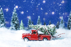 Old Red Truck with Christmas Tree. A miniature replica red pickup truck driving through snow with forest trees blurred in background and Christmas tree tied to stock photos