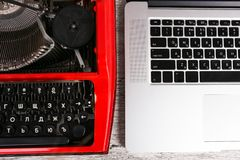Old typewriter maschine and laptop on table. Concept of technology progress. An old red typewriter and a gray notebook on the desk. The concept of technology stock photo
