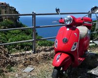 An old red Vespa scooter with sea in the background, Cinque Terre, Italy royalty free stock photography
