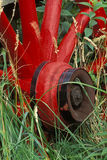 Old Red Wagon Wheel. An old red wagon wheel in a field of tall grass Royalty Free Stock Photos