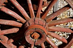 Old red wagon wheel with spokes and hub. The wooden hub, spokes, and axle of an old red wagon wheel Royalty Free Stock Photography
