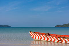 Old Red and White wooden boat left to rot. On a white sand beach in a tropical beach bay Royalty Free Stock Photos