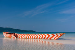 Old Red and White wooden boat left to rot. On a white sand beach in a tropical beach bay Stock Images