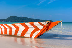 Old Red and White wooden boat left to rot. On a white sand beach in a tropical beach bay Royalty Free Stock Photography