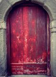 Old red wood door in stone arch. Red old wood planks door in a stone arch Stock Photo