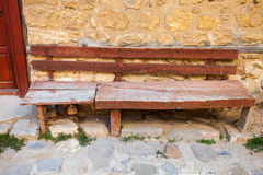 Old red wooden bench near be the stone wall Stock Photo