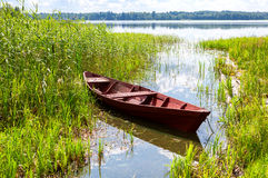 Old red wooden boat at the lake Stock Photography