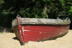 Old red wooden clinker rowboat on a beach Stock Photo