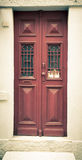 Old red wooden door with window and grid. Toned Stock Images