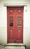 Old red wooden door with window and grid. Toned Royalty Free Stock Image