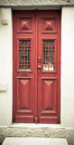 Old red wooden door with window and grid. Toned Royalty Free Stock Photos