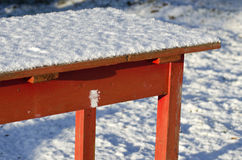 Old red wooden garden table with snow Stock Photo
