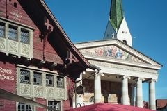 Old red wooden house and parish church Stock Photo