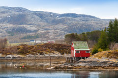 Old red wooden house stands on sea coast Royalty Free Stock Photography