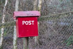 Old red wooden post box in countryside for mail and letters stock photography