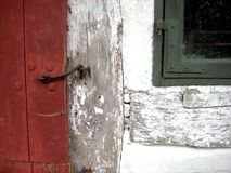 Old red wooden timber door with iron door hinge Whitewashed royalty free stock image