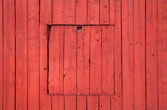 Old red wooden wall with closed square window. Flat background photo texture Royalty Free Stock Images