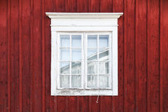 Old red wooden wall with window. In white frame, typically Scandinavian living house architecture detail Stock Photography