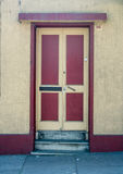 Old red and yellow door. On a grunge wall Stock Images