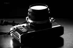 An old reflex camera from the seventies. Laying over a table Royalty Free Stock Images