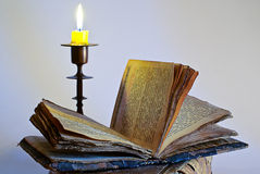 Old religious book and candlestick with candle Royalty Free Stock Images