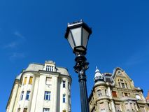Old residential buildings in Budapest with vintage street lamp. Pastel color newly renovated old residential buildings in Budapest with Mansard roofs and black royalty free stock images
