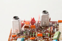 Old resistors capacitors close-up, selective focus. Vintage design circuit board and colorful electronic components Royalty Free Stock Photos