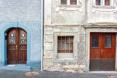 Old and restored nearby. Old wooden door of a shabby demaged house facade. A small town in the mountains of Slovenia. Old wooden door of a shabby demaged house stock photo
