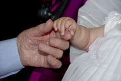 Old retired man hands holding newborn infant one Stock Images