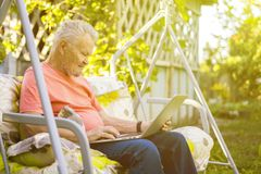 Old retired man working on computer in summer cottage garden royalty free stock photography