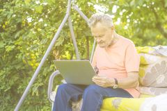 Old retired man working on computer in summer cottage garden stock photos
